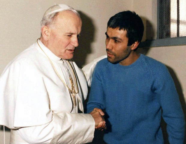 FILE - In this Dec. 27, 1983 file photo provided by Vatican newspaper L'Osservatore Romano, Pope John Paul II, left, meets Mehmet Ali Agca, in Agca's prison cell in Rome. The Vatican says the Turk who shot and wounded John Paul II in 1981 has laid flowers on the saint's tomb in St. Peter's Basilica. A Vatican spokesman, the Rev. Ciro Benedettini, said the surprise visit Saturday by Mehmet Ali Agca lasted a few minutes. As with other flowers left by visitors to the tomb, the white blossoms were later removed by basilica workers. John Paul visited the incarcerated Agca in 1983 and later intervened with Italian authorities to gain Agca's release in 2000 from the Italian prison where he was serving a life sentence for the assassination attempt in St. Peter's Square. (AP Photo/L'Osservatore Romano, File)